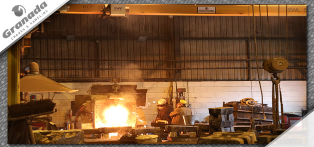 Molten Iron pouring from ladel suspended from an overhead crane